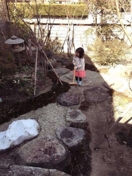 デッキブラシで飛び石を磨く