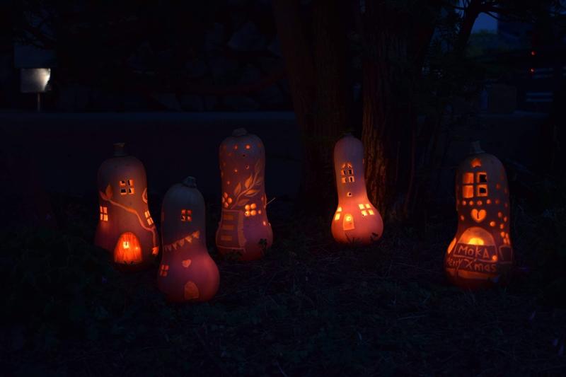 火の入ったかぼちゃランタン。夕暮れに暖かい灯かりが浮かび上がる