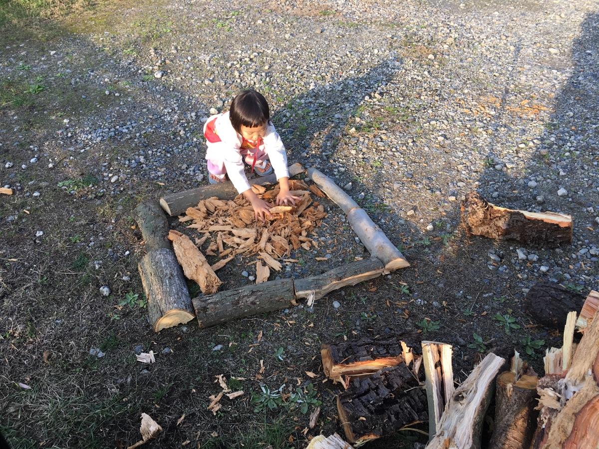 キャンプファイアをしようと薪の端材を並べる子ども